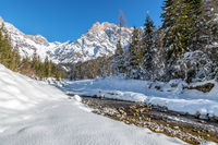 Sunny winter landscape in the alps: Mountain range, river, snowy trees, sunshine and blue sky