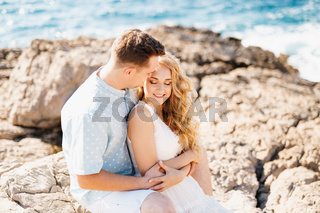 Man and woman in love embracing, smiling and holding hands on the rocky seashore