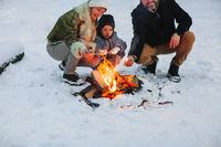 Happy family resting near campfire in winter