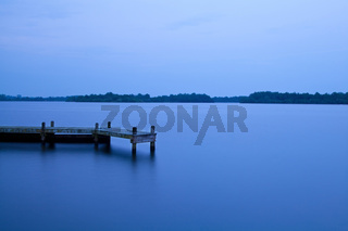 wooden pier on the lake at night