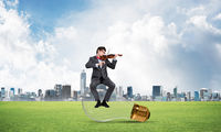 Young businessman plays the violin