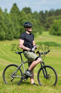 Sportive man mountain biking relax sunny meadows