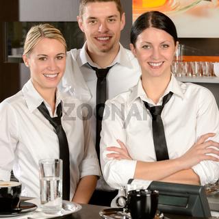 Three server posing in uniform in cafe