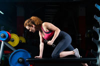 attractive young woman engaged with dumbbells in the gym.