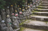 Buddha statues with knitted colorful hats along stairs at the temple Diasho-in in Miyajima, Japan