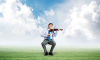 young businessman playing violin