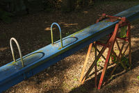Old weathered blue red seesaw in a playground