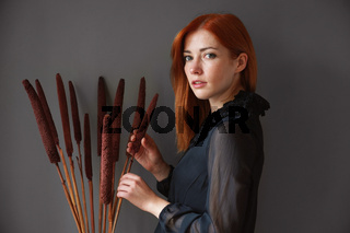 elegant young woman with dried reed flowers
