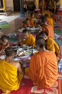 Buddhistische Mönche bei der Einnahme des Mittagsmahls im Refektorium des Klosters Kampong Ampil