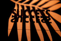 Success word cutting and standing from paper, lit from behind and casting a shadow.