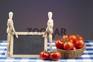 Korb mit Tomaten, Gliederpuppen und Schiefertafel