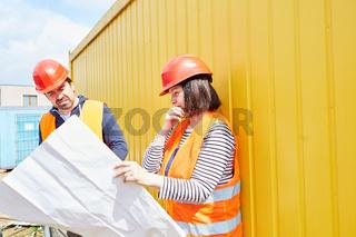 Vorarbeiter und Architektin mit Bauzeichnung