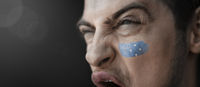 A screaming man with the image of the Federated States Micronesia national flag on his face