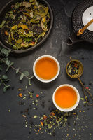 Herbal tea with teapot and herbal leaves on black stone background