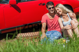 Smiling couple sitting on the grass having picnic together