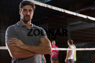 Portrait of confident volleyball player with teammates in background