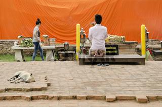 man praying at buddhist shrine ayutthaya thailand