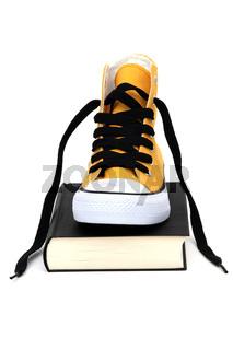Sneaker auf schwarzem Buch
