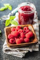 Ripe raspberries in bowl and raspberry jam.