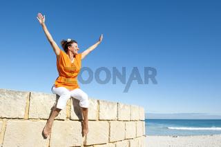 Joyful mature woman ocean background