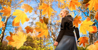 Woman and autumn leaves in the park.