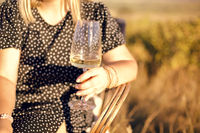 Crop woman with white wine outdoors