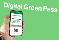 The digital green pass of the european union with the QR code on the screen of a mobile held by a hand with a blurred green background