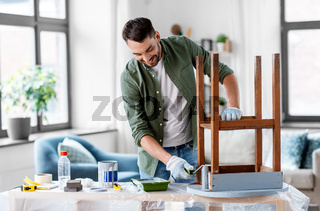 man painting old table in grey color at home