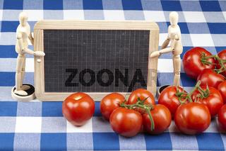 Tomaten mit Gliederpuppen und Schiefertafel