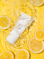 Cosmetic tube in water,lemon slices,yellow bg
