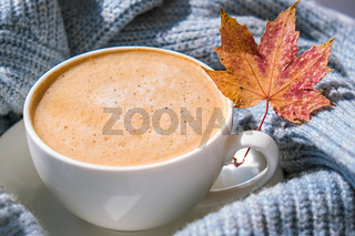 White cup of morning warming coffee on blue knitted sweater with maple yellow leaves background. Cozy home concept. Aesthetics blog lifestyle. Autumn Still life. Cappuccino or latte hot drink