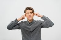 Tired or trying to rethink the information received while experiencing a headache young handsome man in grey shirt look with cool hairstyle isolated on white background