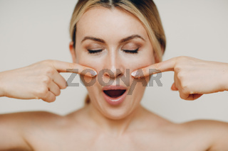 Young adult woman doing facial gymnastics self massage and rejuvenating exercises face building for skin and muscles lifting