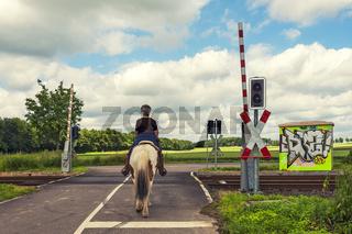 Reiterin auf einem Bahnübergang