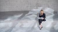 Female entrepreneur using laptop outside concrete building