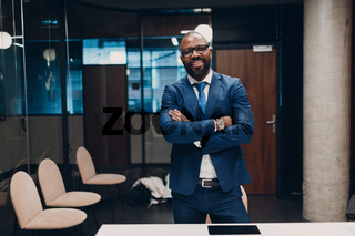 Portrait smiling african american businessman in blue suit in office
