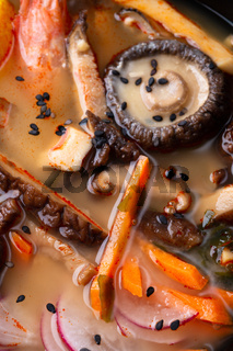 miso soup with mussels, shrimps , shiitake mushrooms and vegatables. macro shot. flat lay