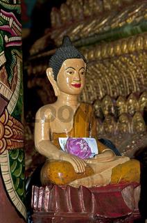 Buddha Figur aus Marmor mit einem Geldschein und einer Lotusblüte als Opfergaben  im Inneren der Pagode des buddhistischen Wat Phnom Tempels