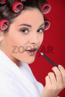 Woman wearing rollers and applying lip gloss