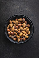 Unpeeled hazelnuts and almonds. Sweet nuts in bowl.