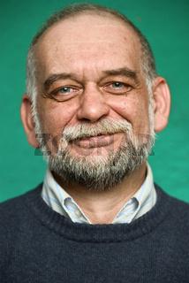 Portrait of the elderly man on green background.