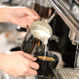 Waitress hands pouring milk making cappuccino