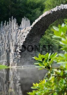 Brücke spiegelt sich im Wasser (Rakotzbrücke Kromlau), Hochformat