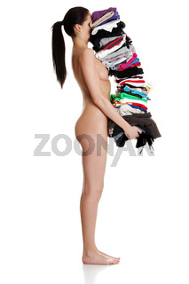 Young naked woman is holding clothes.