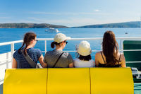 Family - mother with three daughters - on the ferry. The beginning of vacation - sea journey