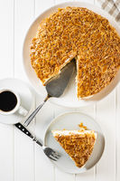 Sliced sweet almond cake on plate. Pie with cream and almonds.