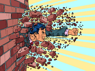 Businessman breaks through a brick wall. The will to overcome obstacles