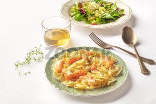Pasta and wine, Italian dinner. Farfalle with smoked salmon and cream sauce