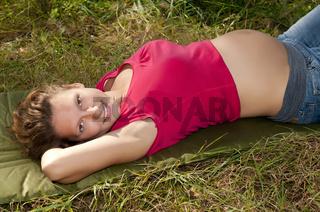 schwangere junge frau entspannt sich auf einer wiese