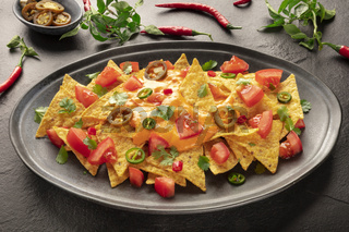 Mexican nachos with a cheese sauce, chili and jalapeno peppers, tomatoes, and cilantro leaves